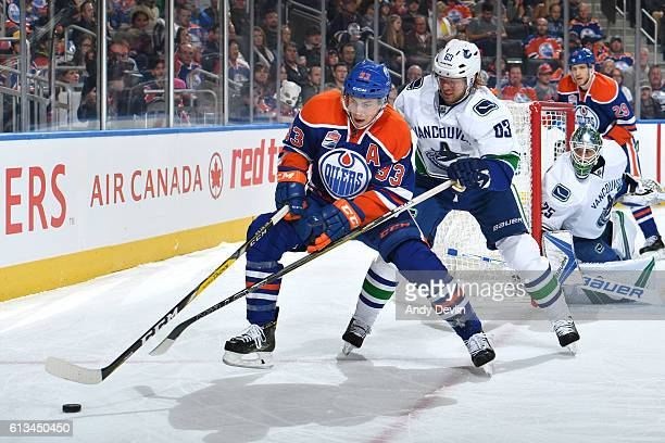 Ryan NugentHopkins of the Edmonton Oilers battles for the puck against Philip Larsen of the Vancouver Canucks on October 8 2016 at Rogers Place in...