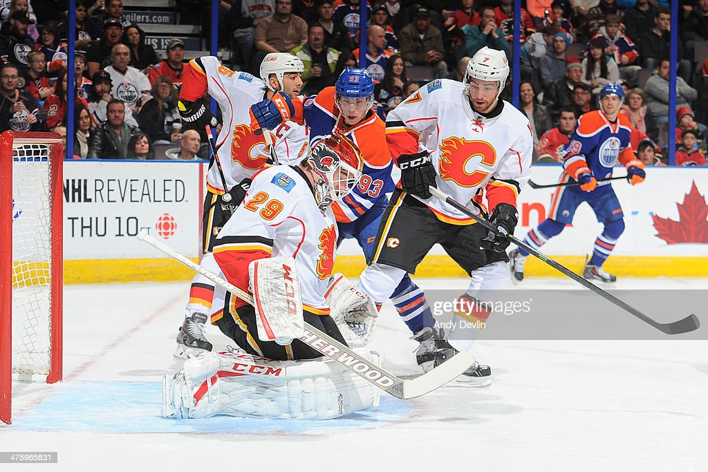 <a gi-track='captionPersonalityLinkClicked' href=/galleries/search?phrase=Ryan+Nugent-Hopkins&family=editorial&specificpeople=7144190 ng-click='$event.stopPropagation()'>Ryan Nugent-Hopkins</a> #93 of the Edmonton Oilers battles for the puck against T.J. Brodie #7 and <a gi-track='captionPersonalityLinkClicked' href=/galleries/search?phrase=Reto+Berra&family=editorial&specificpeople=570422 ng-click='$event.stopPropagation()'>Reto Berra</a> #29 of the Calgary Flames on March 1, 2014 at Rexall Place in Edmonton, Alberta, Canada.