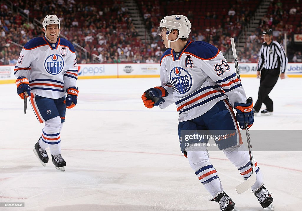 <a gi-track='captionPersonalityLinkClicked' href=/galleries/search?phrase=Ryan+Nugent-Hopkins&family=editorial&specificpeople=7144190 ng-click='$event.stopPropagation()'>Ryan Nugent-Hopkins</a> #93 of the Edmonton Oilers celebrates alongside <a gi-track='captionPersonalityLinkClicked' href=/galleries/search?phrase=Andrew+Ference&family=editorial&specificpeople=202264 ng-click='$event.stopPropagation()'>Andrew Ference</a> #21 after Ryan Jones (not pictured) scored a third period goal against the Phoenix Coyotes during the NHL game at Jobing.com Arena on October 26, 2013 in Glendale, Arizona. The Coyotes defeated the Oilers 5-4.