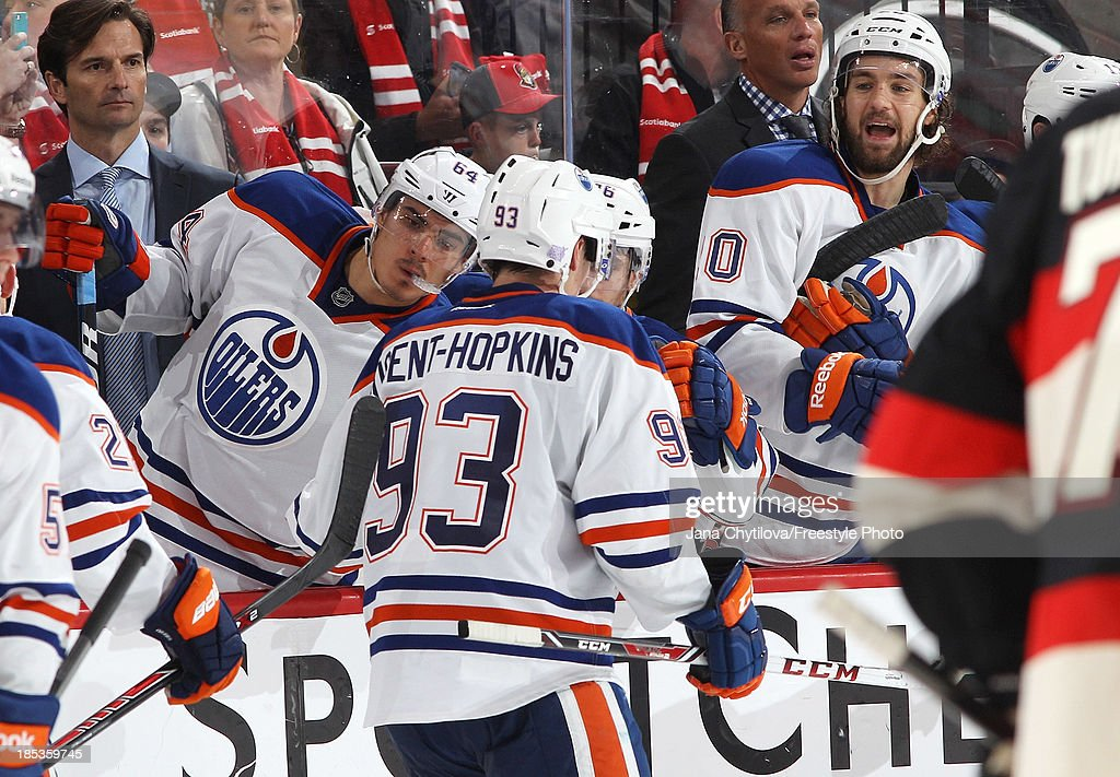 <a gi-track='captionPersonalityLinkClicked' href=/galleries/search?phrase=Ryan+Nugent-Hopkins&family=editorial&specificpeople=7144190 ng-click='$event.stopPropagation()'>Ryan Nugent-Hopkins</a> #93 of the Edmonton Oilers celebrates his empty net goal with teammates <a gi-track='captionPersonalityLinkClicked' href=/galleries/search?phrase=Nail+Yakupov&family=editorial&specificpeople=7419136 ng-click='$event.stopPropagation()'>Nail Yakupov</a> #64 and <a gi-track='captionPersonalityLinkClicked' href=/galleries/search?phrase=Luke+Gazdic&family=editorial&specificpeople=4754039 ng-click='$event.stopPropagation()'>Luke Gazdic</a> #20 against the Ottawa Senators during an NHL game at Canadian Tire Centre on October 19, 2013 in Ottawa, Ontario, Canada.
