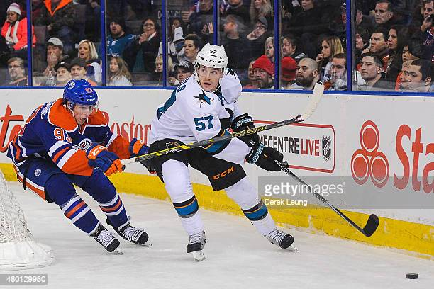 Ryan NugentHopkins of the Edmonton Oilers chases Tommy Wingels of the San Jose Sharks during an NHL game at Rexall Place on December 7 2014 in...