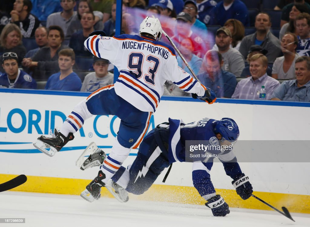 <a gi-track='captionPersonalityLinkClicked' href=/galleries/search?phrase=Ryan+Nugent-Hopkins&family=editorial&specificpeople=7144190 ng-click='$event.stopPropagation()'>Ryan Nugent-Hopkins</a> #93 of the Edmonton Oilers collides with <a gi-track='captionPersonalityLinkClicked' href=/galleries/search?phrase=Radko+Gudas&family=editorial&specificpeople=5648763 ng-click='$event.stopPropagation()'>Radko Gudas</a> #7 of the Tampa Bay Lightning during the third period as they battle for the puck at Tampa Bay Times Forum on November 7, 2013 in Tampa, Florida.