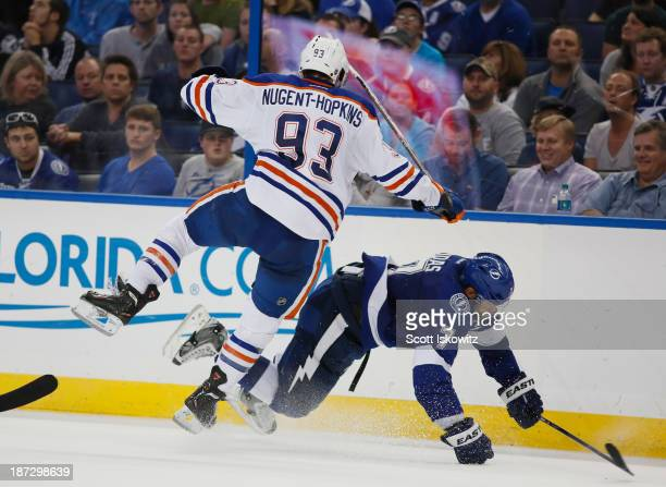 Ryan NugentHopkins of the Edmonton Oilers collides with Radko Gudas of the Tampa Bay Lightning during the third period as they battle for the puck at...
