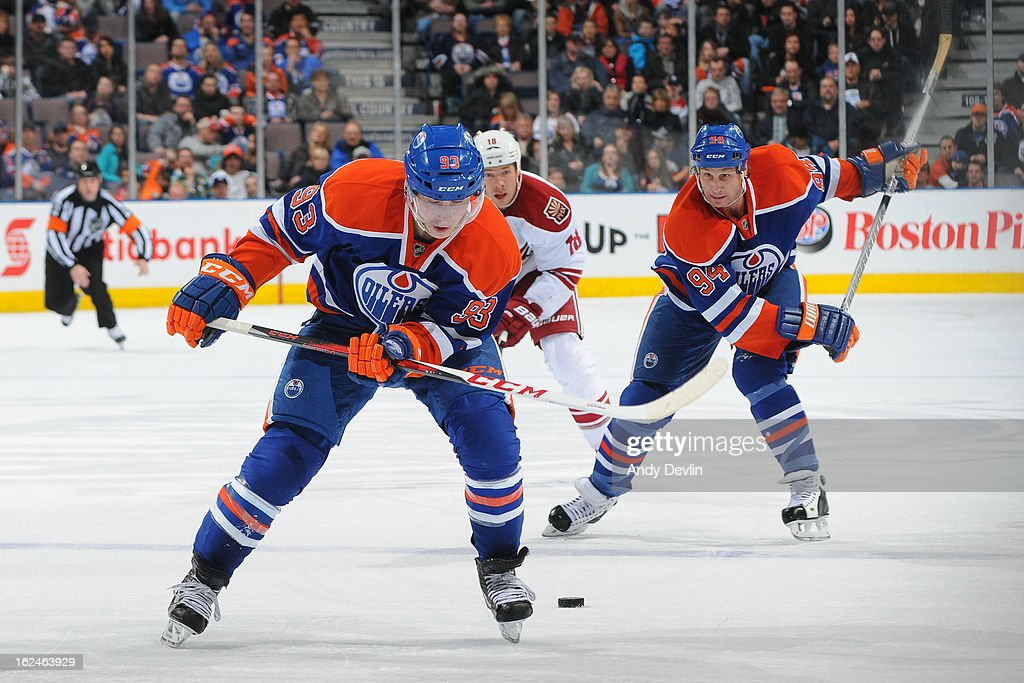 <a gi-track='captionPersonalityLinkClicked' href=/galleries/search?phrase=Ryan+Nugent-Hopkins&family=editorial&specificpeople=7144190 ng-click='$event.stopPropagation()'>Ryan Nugent-Hopkins</a> #93 of the Edmonton Oilers drops the puck back to teammate <a gi-track='captionPersonalityLinkClicked' href=/galleries/search?phrase=Ryan+Smyth+-+Giocatore+di+hockey+su+ghiaccio&family=editorial&specificpeople=202567 ng-click='$event.stopPropagation()'>Ryan Smyth</a> #94 in a game against the Phoenix Coyotes on February 23, 2013 at Rexall Place in Edmonton, Alberta, Canada.