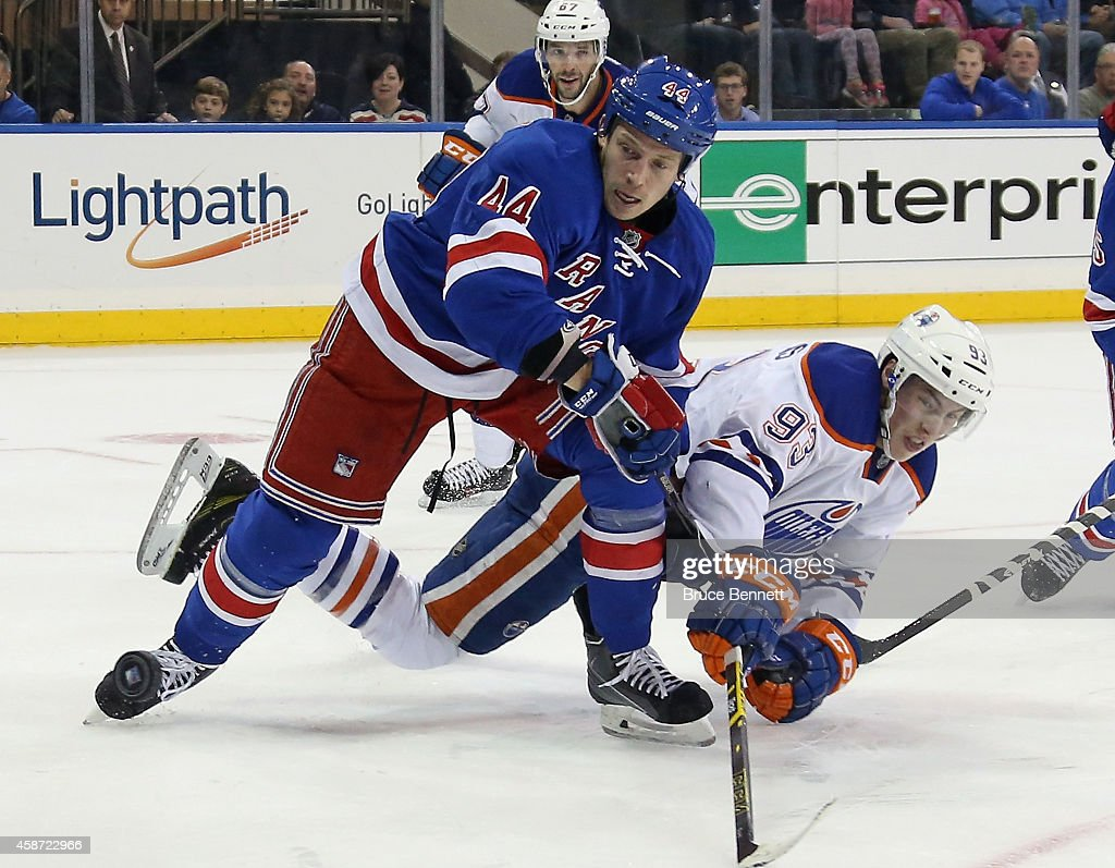 Ryan Nugent-Hopkins #93 of the Edmonton Oilers is knocked down by Matt Hunwick #44 of the New York Rangers during the first period at Madison Square Garden on November 9, 2014 in New York City. The Oilers defeated the Rangers 3-1.