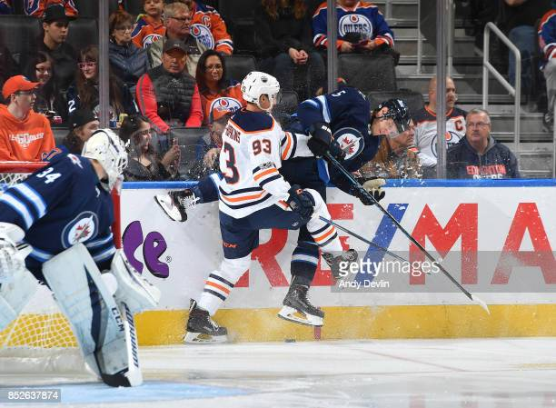 Ryan NugentHopkins of the Edmonton Oilers lands a hit on Dmitry Kulikov of the Winnipeg Jets on September 23 2017 at Rogers Place in Edmonton Alberta...