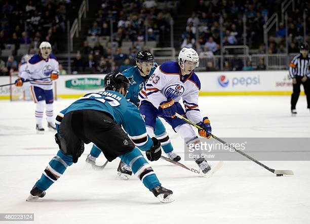 Ryan NugentHopkins of the Edmonton Oilers looks to pass around Scott Hannan of the San Jose Sharks at SAP Center on December 9 2014 in San Jose...