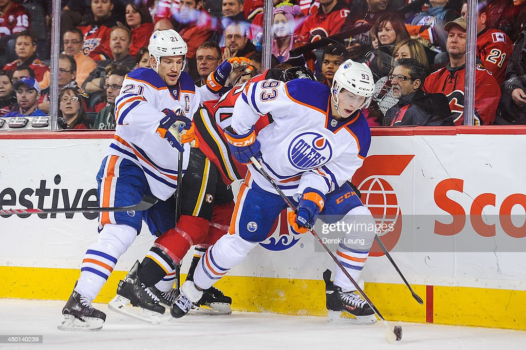 <a gi-track='captionPersonalityLinkClicked' href=/galleries/search?phrase=Ryan+Nugent-Hopkins&family=editorial&specificpeople=7144190 ng-click='$event.stopPropagation()'>Ryan Nugent-Hopkins</a> #93 of the Edmonton Oilers skates with the puck against David Jones #54 of the Calgary Flames during an NHL game at Scotiabank Saddledome on November 16, 2013 in Calgary, Alberta, Canada.