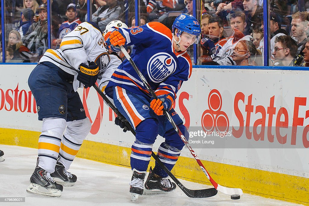 Ryan Nugent-Hopkins #93 of the Edmonton Oilers skates with the puck against Matt Ellis #37 of the Buffalo Sabres during an NHL game at Rexall Place on March 20, 2014 in Edmonton, Alberta, Canada. The Sabres defeated the Oilers 3-1.