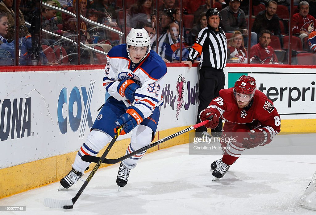 Ryan Nugent-Hopkins #93 of the Edmonton Oilers skates with the puck under pressure from Mikkel Boedker #89 of the Arizona Coyotes during the third period of the NHL game at Gila River Arena on December 16, 2014 in Glendale, Arizona. The Coyotes defeated the Oilers 2-1 in overtime.