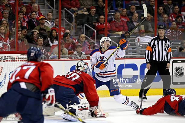 Ryan NugentHopkins of the Edmonton Oilers tries to shoot as the puck bounces into the air on goalie Braden Holtby of the Washington Capitals in the...
