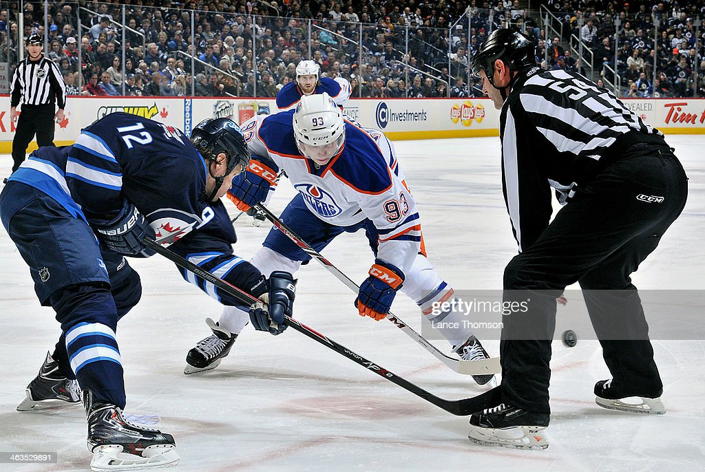 <a gi-track='captionPersonalityLinkClicked' href=/galleries/search?phrase=Ryan+Nugent-Hopkins&family=editorial&specificpeople=7144190 ng-click='$event.stopPropagation()'>Ryan Nugent-Hopkins</a> #93 of the Edmonton Oilers wins a third period face-off against <a gi-track='captionPersonalityLinkClicked' href=/galleries/search?phrase=Olli+Jokinen&family=editorial&specificpeople=202946 ng-click='$event.stopPropagation()'>Olli Jokinen</a> #12 of the Winnipeg Jets at the MTS Centre on January 18, 2014 in Winnipeg, Manitoba, Canada.