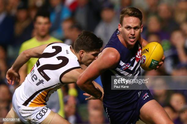 Ryan Nyhuis of the Dockers evades a tackle by Luke Breust of the Hawks during the round 18 AFL match between the Fremantle Dockers and the Hawthorn...