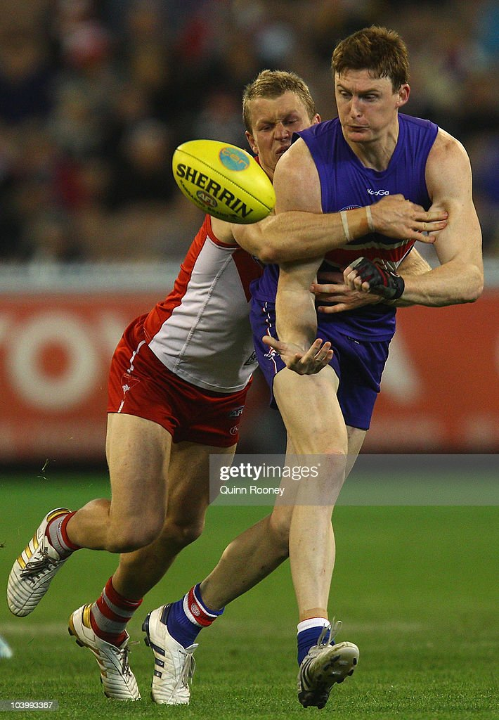 Ryan O'Keefe of the Swans tackles Tom Williams of the Bulldogs as he handballs during the AFL First Semi Final match between the Western Bulldogs and the Sydney Swans at Melbourne Cricket Ground on September 11, 2010 in Melbourne, Australia.