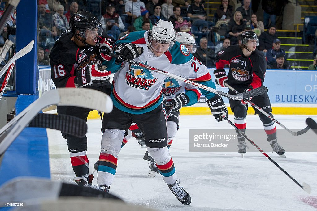 Ryan Olsen #27 of the Kelowna Rockets checks Klarc Wilson #16 of the Prince George Cougars into the boards during first period on February 25, 2014 at Prospera Place in Kelowna, British Columbia, Canada.