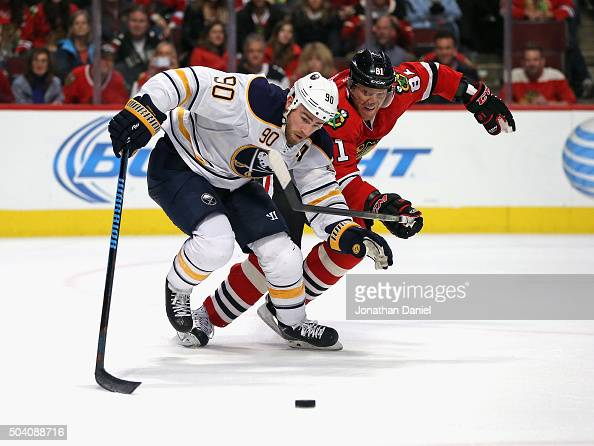 Ryan O'Reilly of the Buffalo Sabres and Marian Hossa of the Chicago Blackhawks chase the puck at the United Center on January 8 2016 in Chicago...