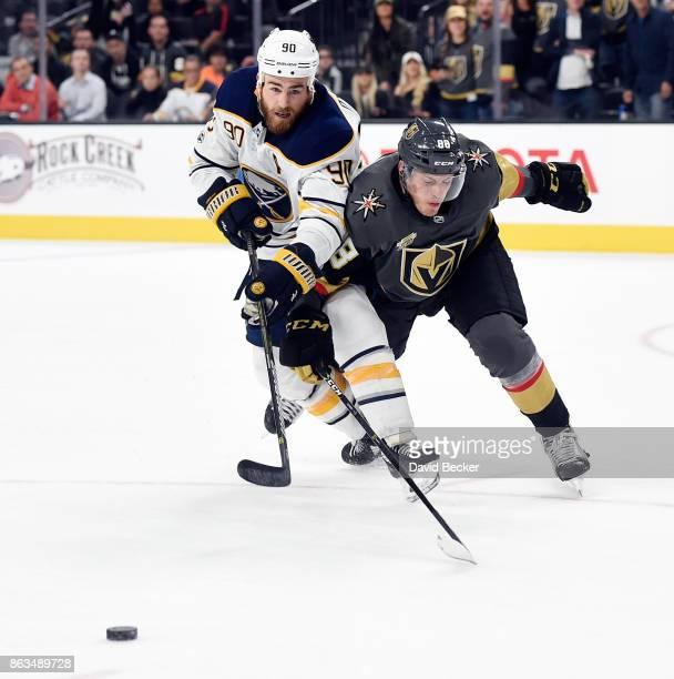 Ryan O'Reilly of the Buffalo Sabres and Nate Schmidt of the Vegas Golden Knights battle for the puck at TMobile Arena on October 17 2017 in Las Vegas...