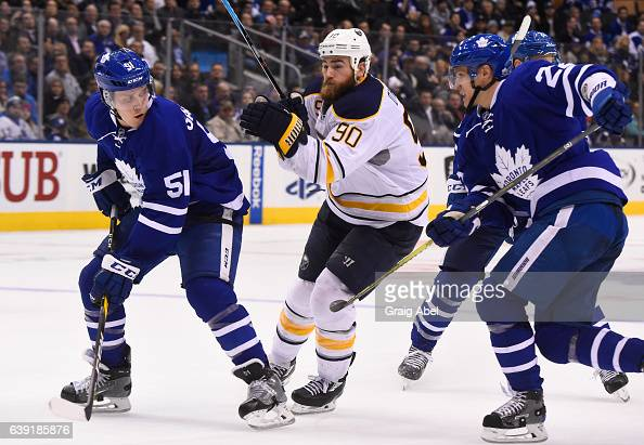 Ryan O'Reilly of the Buffalo Sabres attempts to get between Jake Gardiner and Nikita Zaitsev of the Toronto Maple Leafs during the third period at...