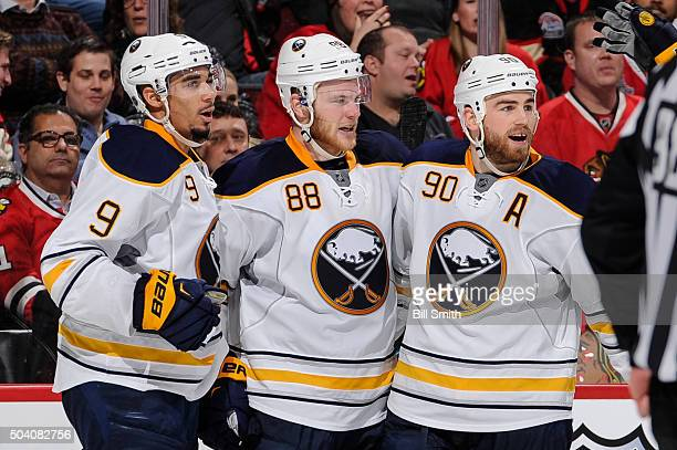 Ryan O'Reilly of the Buffalo Sabres celebrates with Evander Kane and Jamie McGinn after scoring against the Chicago Blackhawks in the third period of...