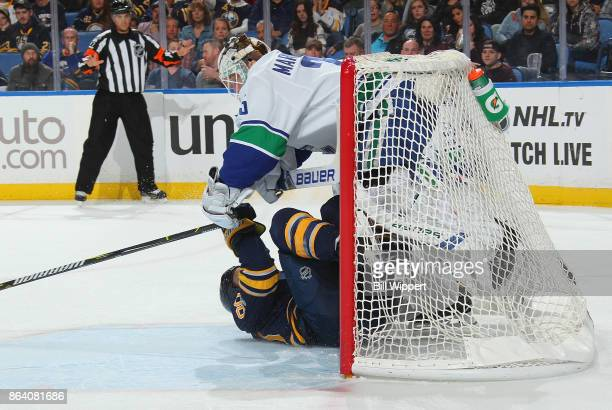 Ryan O'Reilly of the Buffalo Sabres collides with Jacob Markstrom of the Vancouver Canucks during an NHL game on October 20 2017 at KeyBank Center in...
