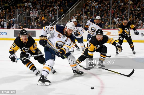 Ryan O'Reilly of the Buffalo Sabres handles the puck between Carl Hagelin and Olli Maatta of the Pittsburgh Penguins at PPG Paints Arena on November...