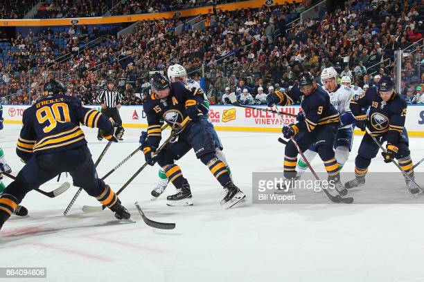 Ryan O'Reilly of the Buffalo Sabres has his stick broken on a faceoff against the Vancouver Canucks while Jack Eichel Evander Kane and Jake McCabe...