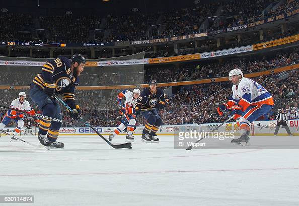 Ryan O'Reilly of the Buffalo Sabres is defended by Johnny Boychuk of the New York Islanders during an NHL game at the KeyBank Center on December 16...