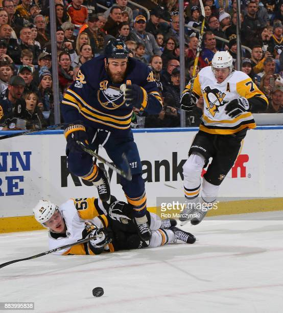 Ryan O'Reilly of the Buffalo Sabres jumps over Jake Guentzel and away from Evgeni Malkin of the Pittsburgh Penguins in pursuit of the puck during an...
