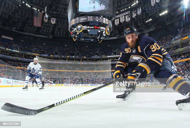 Ryan O'Reilly of the Buffalo Sabres reaches for the puck against the Toronto Maple Leafs during an NHL game at the KeyBank Center on April 3 2017 in...