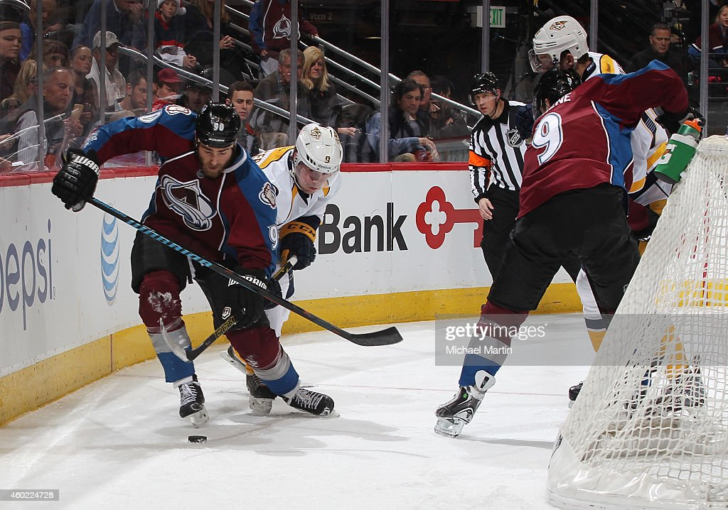 Ryan O'Reilly #90 of the Colorado Avalanche and Filip Forsberg #9 of the Nashville Predators battle for the puck behind the net at the Pepsi Center on December 9, 2014 in Denver, Colorado. The Predators defeated the Avalanche 3-0.