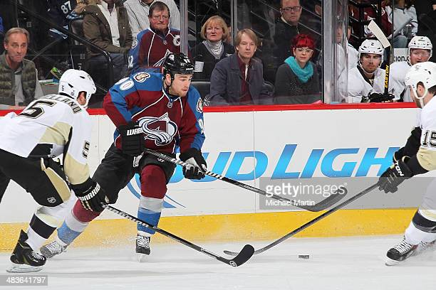Ryan O'Reilly of the Colorado Avalanche skates to the puck as Tanner Glass and Deryk Engelland of the Pittsburgh Penguins close in at the Pepsi...
