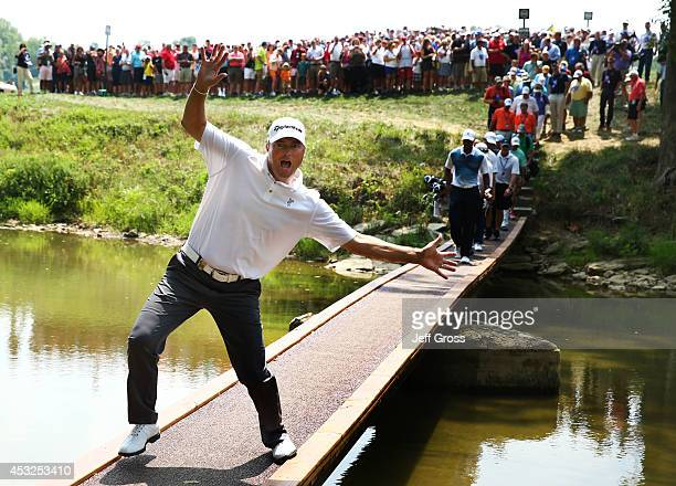 Ryan Palmer of the United States jokingly poses for photograph as Tiger Woods of the United States crosses a bridge during a practice round prior to...