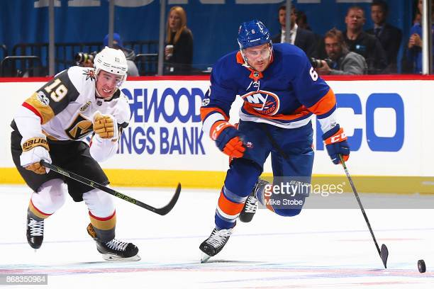 Ryan Pulock of the New York Islanders races up ice with the puck as Reilly Smith of the Vegas Golden Knights gives chase at Barclays Center on...