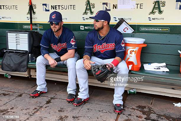 Ryan Raburn and Mike Aviles of the Cleveland Indians are seen in the dugout before the game against the Oakland Athletics on Sunday August 18 2013 at...