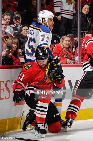 Ryan Reaves of the St Louis Blues and Andrew Desjardins of the Chicago Blackhawks get physical by the boards in the first period of the NHL game at...