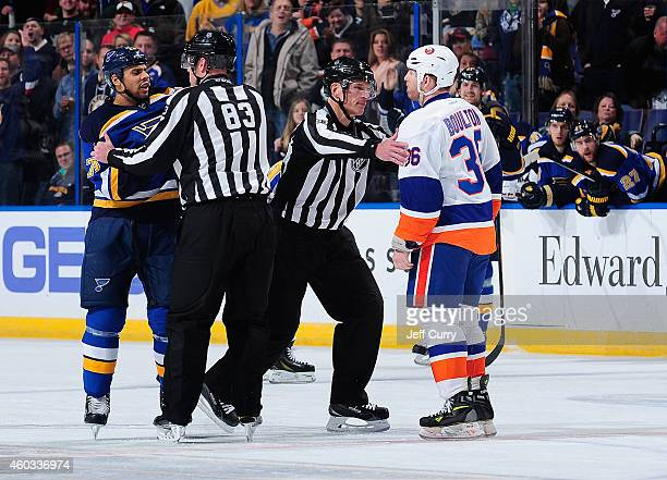 Ryan Reaves of the St Louis Blues and Eric Boulton of the New York Islanders are separated by referee Chris Lee and linesman Brian Murphy on December...