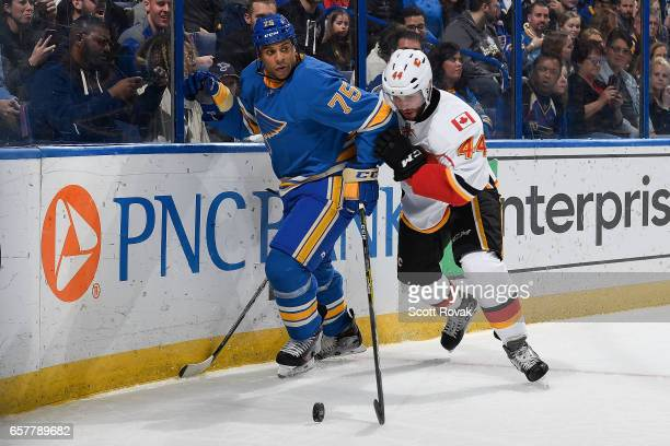 Ryan Reaves of the St Louis Blues and Matt Bartkowski of the Calgary Flames battle for the puck on March 25 2017 at Scottrade Center in St Louis...