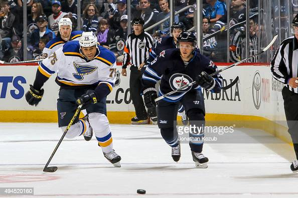 Ryan Reaves of the St Louis Blues and Toby Enstrom of the Winnipeg Jets chase the loose puck down the ice during first period action at the MTS...