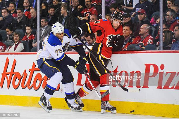 Ryan Reaves of the St Louis Blues checks Chris Butler of the Calgary Flames during an NHL game at Scotiabank Saddledome on January 9 2014 in Calgary...