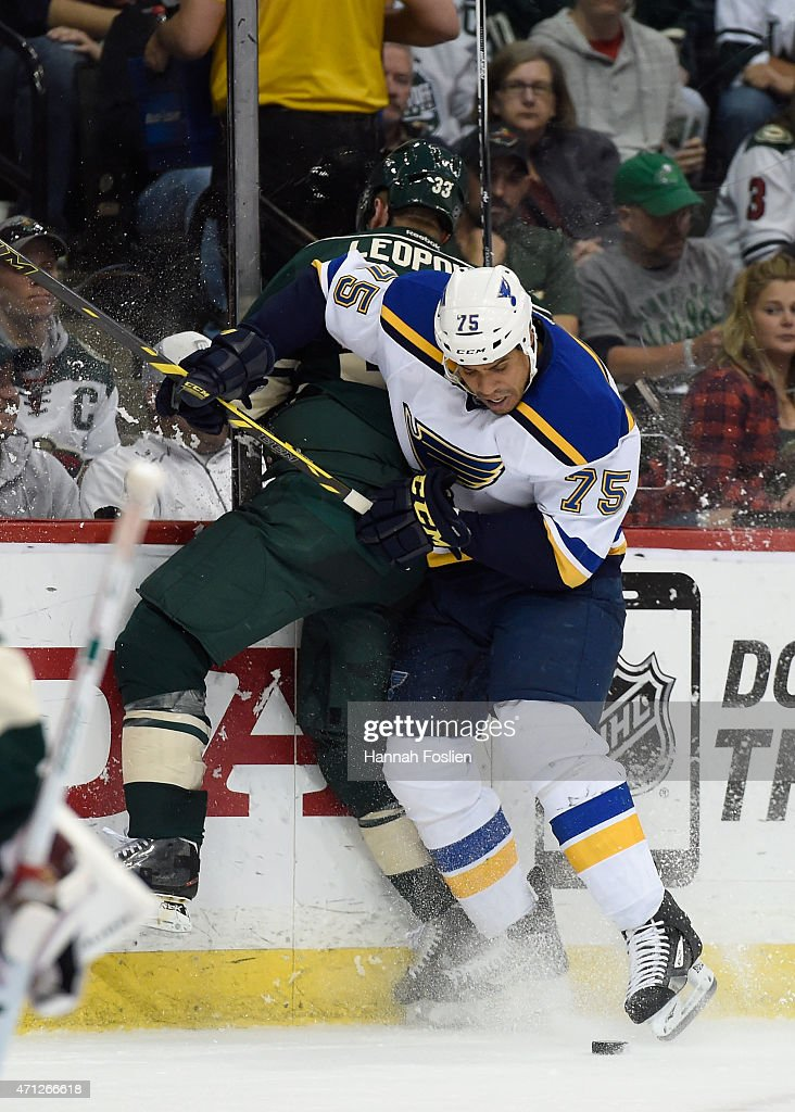 Ryan Reaves of the St Louis Blues checks Jordan Leopold of the Minnesota Wild into the boards during the second period in Game Six of the Western...