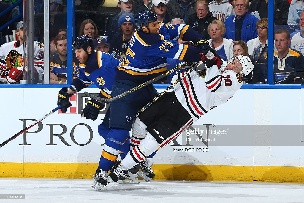 Ryan Reaves of the St Louis Blues checks Patrick Sharp of the Chicago Blackhawks at the Scottrade Center on February 8 2015 in St Louis Missouri
