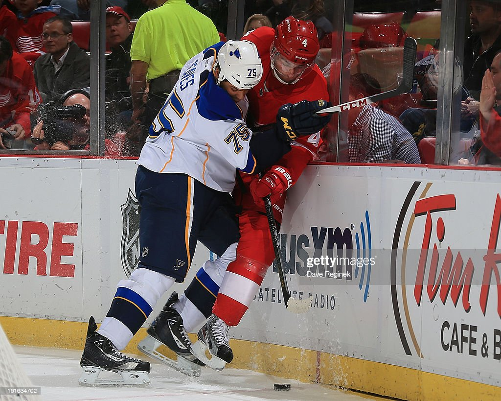 Ryan Reeves #75 of the St Louis Blues body checks Jakub Kindl #4 of the Detroit Red Wings during a NHL game at Joe Louis Arena on February 13, 2013 in Detroit, Michigan.