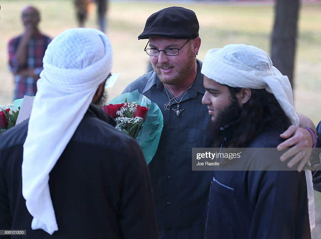 Ryan Reyes (C) speaks with Nizaam Ali (L) and Rahemaan Ali who came to pay their respects during a memorial service at the Santa Fe Dam Recreation Area for Ryan's partner Larry Daniel Kaufman who was killed during a mass shooting at the Inland Regional Center on December 5, 2015 in Irwindale, California. Police continue to investigate the mass shooting at the Inland Regional Center in San Bernardino that left at least 14 people dead and another 17 injured on December 2nd.