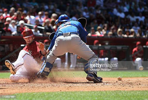 Ryan Roberts of the Arizona Diamondbacks safely slides in to score a run past the tag from catcher Geovany Soto of the Chicago Cubs during the fourth...