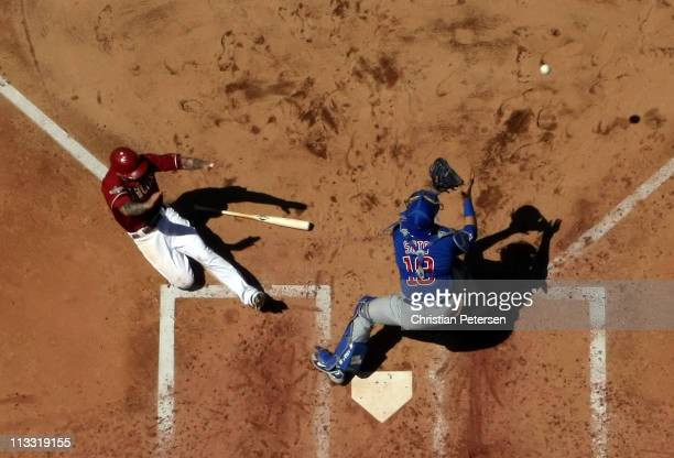 Ryan Roberts of the Arizona Diamondbacks safely slides in to score a run past catcher Geovany Soto of the Chicago Cubs during the fourth inning of...