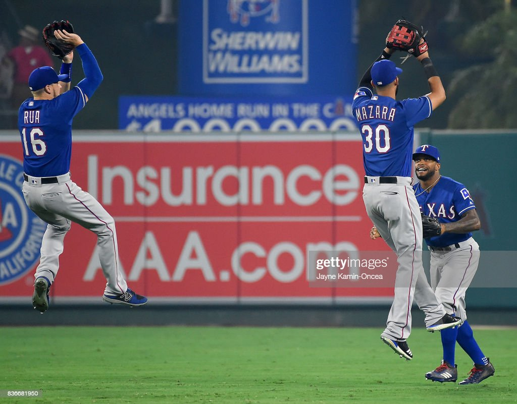 Ryan Rua #16, Delino DeShields #3 and Nomar Mazara #30 of the Texas Rangers celebrate in the outfield after the final out of the ninth inning of the game against the Los Angeles Angels of Anaheim at Angel Stadium of Anaheim on August 21, 2017 in Anaheim, California.