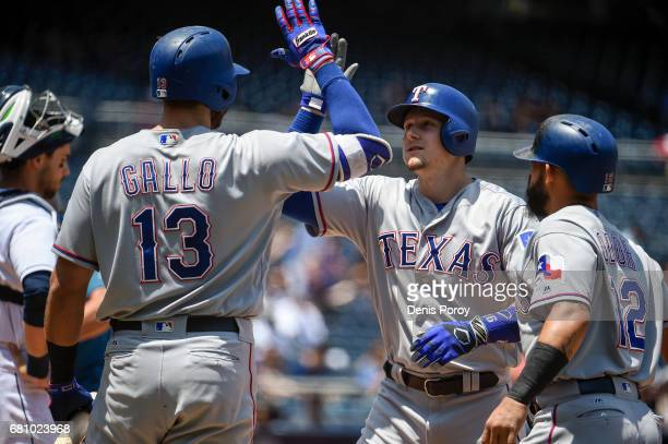 Ryan Rua of the Texas Rangers center is congratulated by Joey Gallo and Rougned Odor after he hit a threerun home run during the first inning of a...