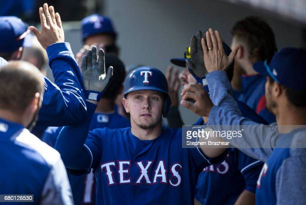 Ryan Rua of the Texas Rangers is congratulated in the dugout aftter scoring on a sacrifice fly by Delino DeShields of the Texas Rangers off relief...