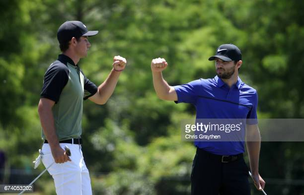 Ryan Ruffels of Australia and Kyle Stanley react after making their put on the seventh hole plays his shot from the eighth tee during the first round...