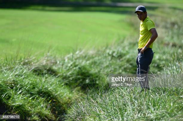 Ryan Ruffels of Australia looks for his ball on the eighth hole during the first round of the Wyndham Championship at Sedgefield Country Club on...